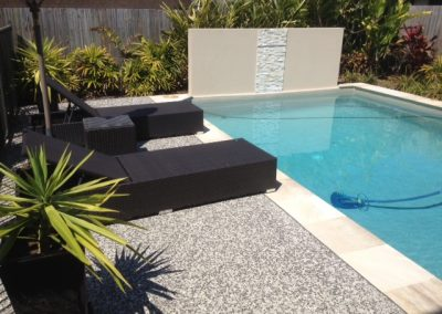 Exposed aggregate pool paving with natural stone coping