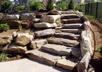 Natural stone retaining walls using boulders