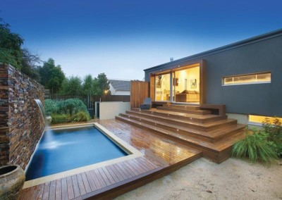 Timber decking with a natural stone feature wall along with outdoor lighting