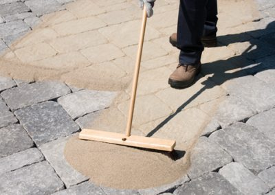 Spreading polymeric sand into the interlocking pavers